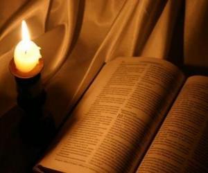 Die Bibel und eine brennende kerze auf dem altar puzzle