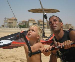 Kind macht einen Drachen steigen mit seinem Vater puzzle