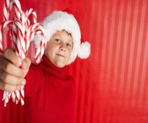Kind mit Hut von Santa Claus und Zuckerstangen in der Hand puzzle