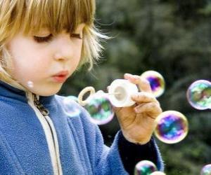 Kind spielt, um Seifenblasen blasen puzzle
