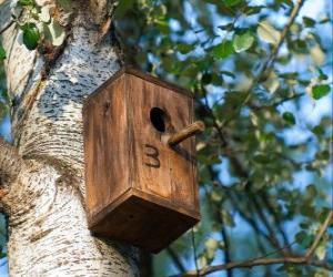 Kleines Haus aus Holz für die Vögel im Frühjahr puzzle