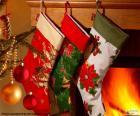 Weihnachtssocken mit dekoration und hängen an der wand die kamin