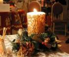Kerze als mittelpunkt mit zweigen der stechpalme und tannen geschmückt