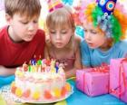 Mädchen im Moment der Ausblasen der Kerzen auf ihrem Geburtstagskuchen