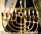 Neunarmige leuchter  mit beleuchteten Kerzen, ein Chanukkia verwendet in den Chanukkafest