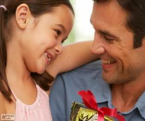 Vater mit seiner Tochter, während sie das Geschenk geben wird puzzle