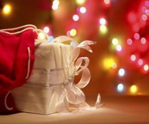 Weihnachtsgeschenk eingepackt in weißes Papier und verziert mit einem Bogen puzzle